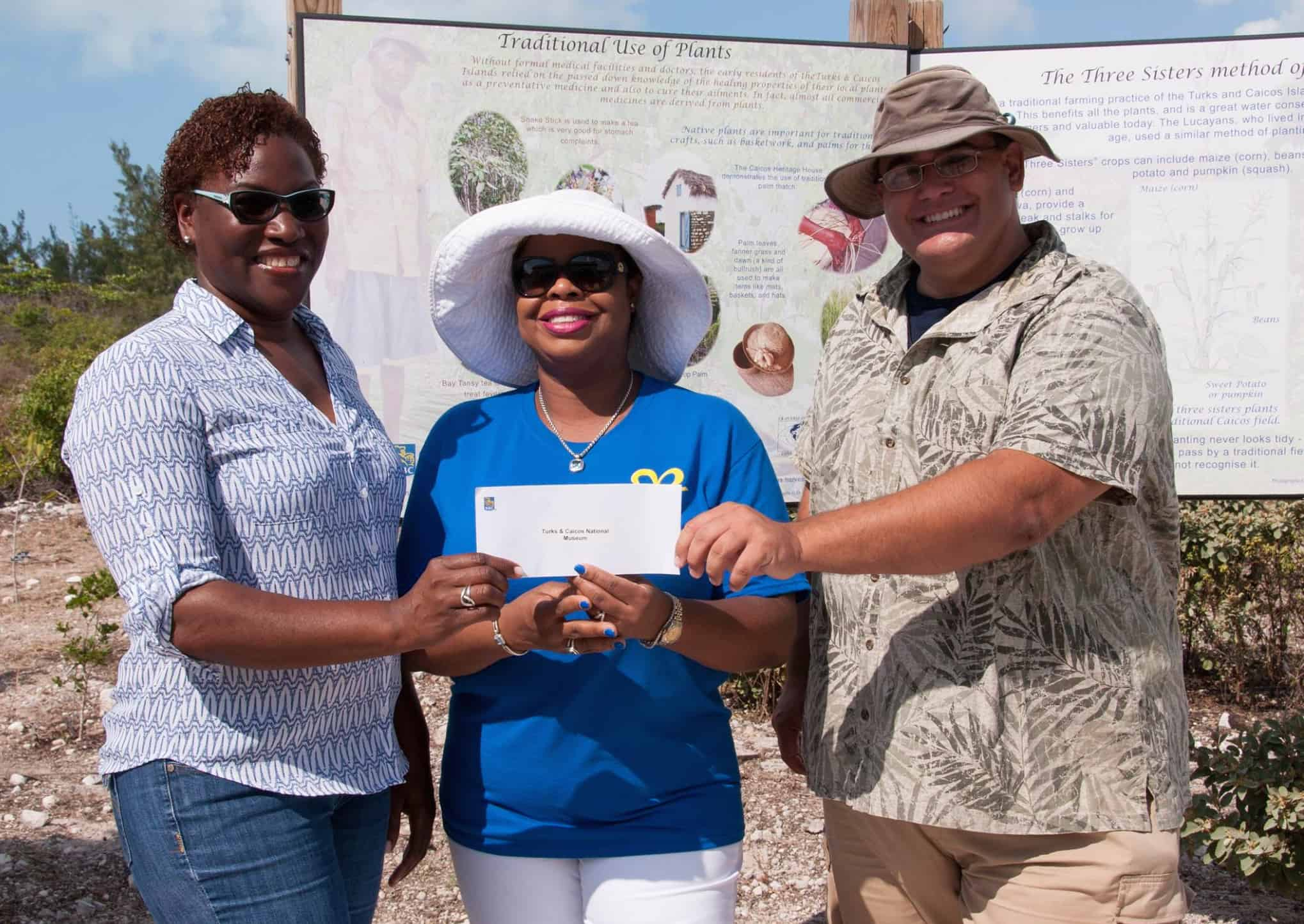 Candianne Williams (Manager, Turks and Caicos National Museum, Providenciales) and Bryan Naqqi Manco (DECR and TCNM) are presented with a cheque from Sanfra Foster (Manager, Royal Bank of Canada, Providenciales) [centre]