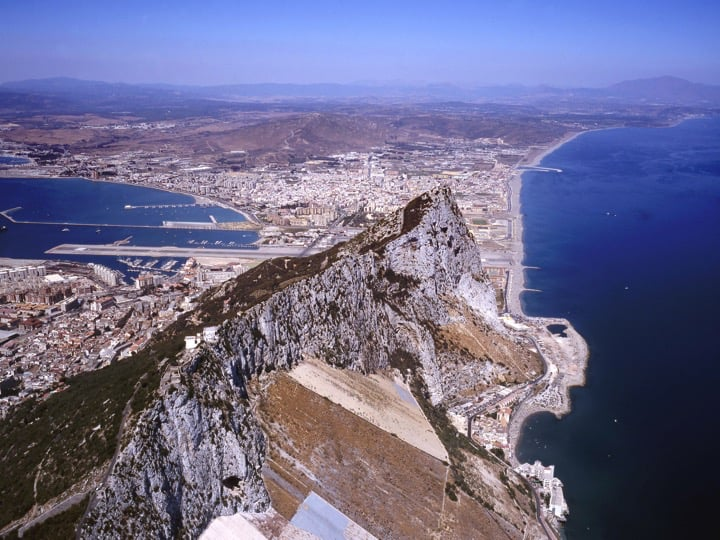 Looking to the north, with steep eastern slopes to the right, the town to the left, and the airport runway and Spain beyond the Rock;Copyright: HM Government of Gibraltar (HMGOG) / Gibraltar Ornithological & Natural History Society (GONHS).